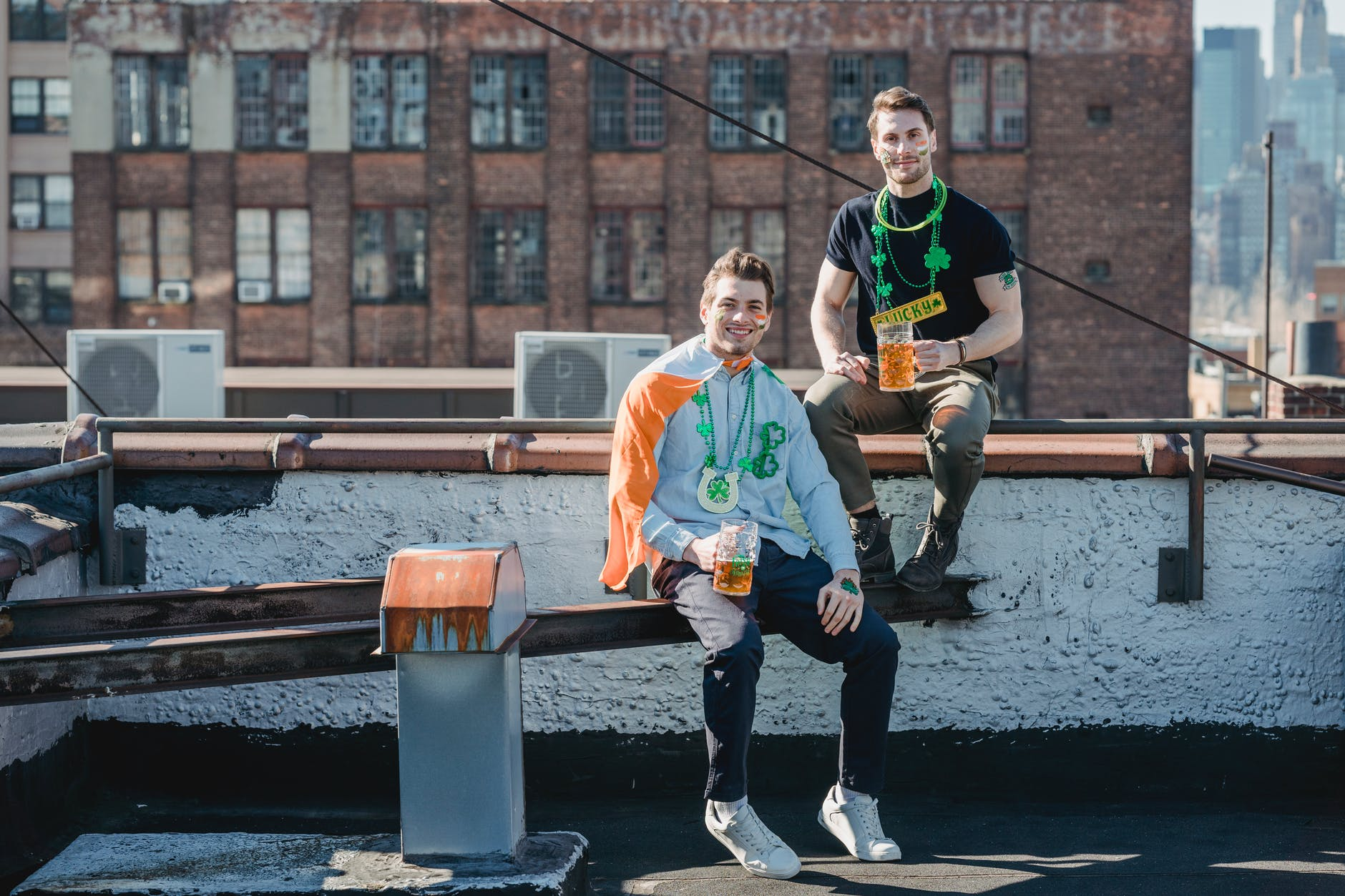 cheerful young men boozing on terrace while celebrating st patricks day